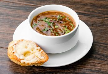 Five Onion Soup in a bowl with bread