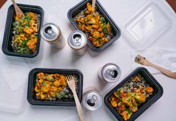 Overhead table shot of Masala Curry in takeout-style containers with cans of sparking water.