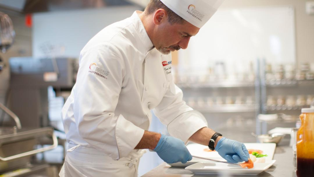 Chef Thomas Andresakes plating a dish in the kitchen