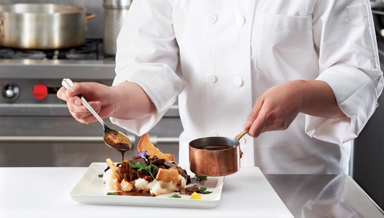 A chef uses a spoon to top a beef dish with gravy.