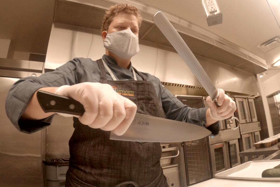 A chef sharpening their knife while wearing Personal Protective Equipment.