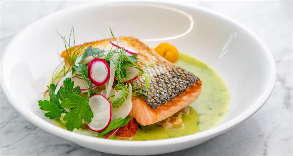 Pan-roasted salmon with pesto brodo garnished with parsley and radish