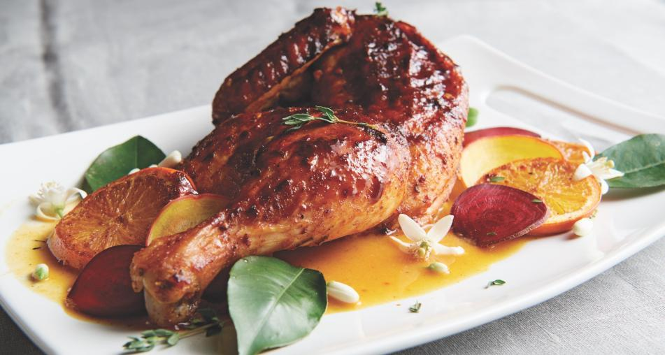 Orange Chipotle Roasted Chicken on a plate with garnish
