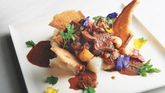 Beef Bourguignon Toast on a plate with colorful garnish