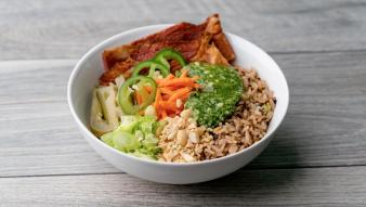 A bahn mi bowl containing jalapeños, carrots, rice, pork, and peanuts topped with Minor's® Gluten Free GreenLeaf Basil Pesto