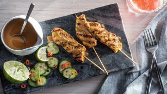 Chicken skewers with sauce and cucumbers